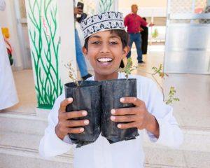 boy with boswellia sacra seedling